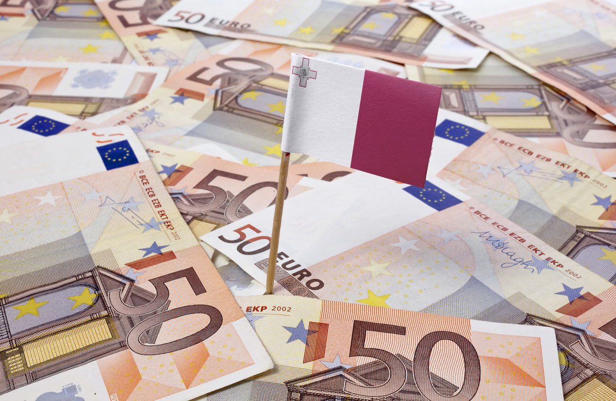 Flag of Malta sticking in european bank notes.